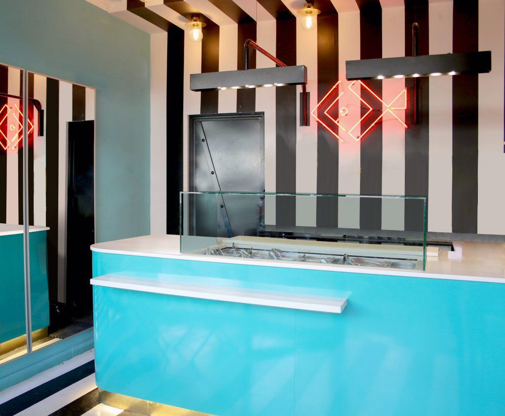 Restaurante de take away de comida peruana reformado con pared a rayas negras y blancas y barra de metal de color turquesa en contraste con el espacio