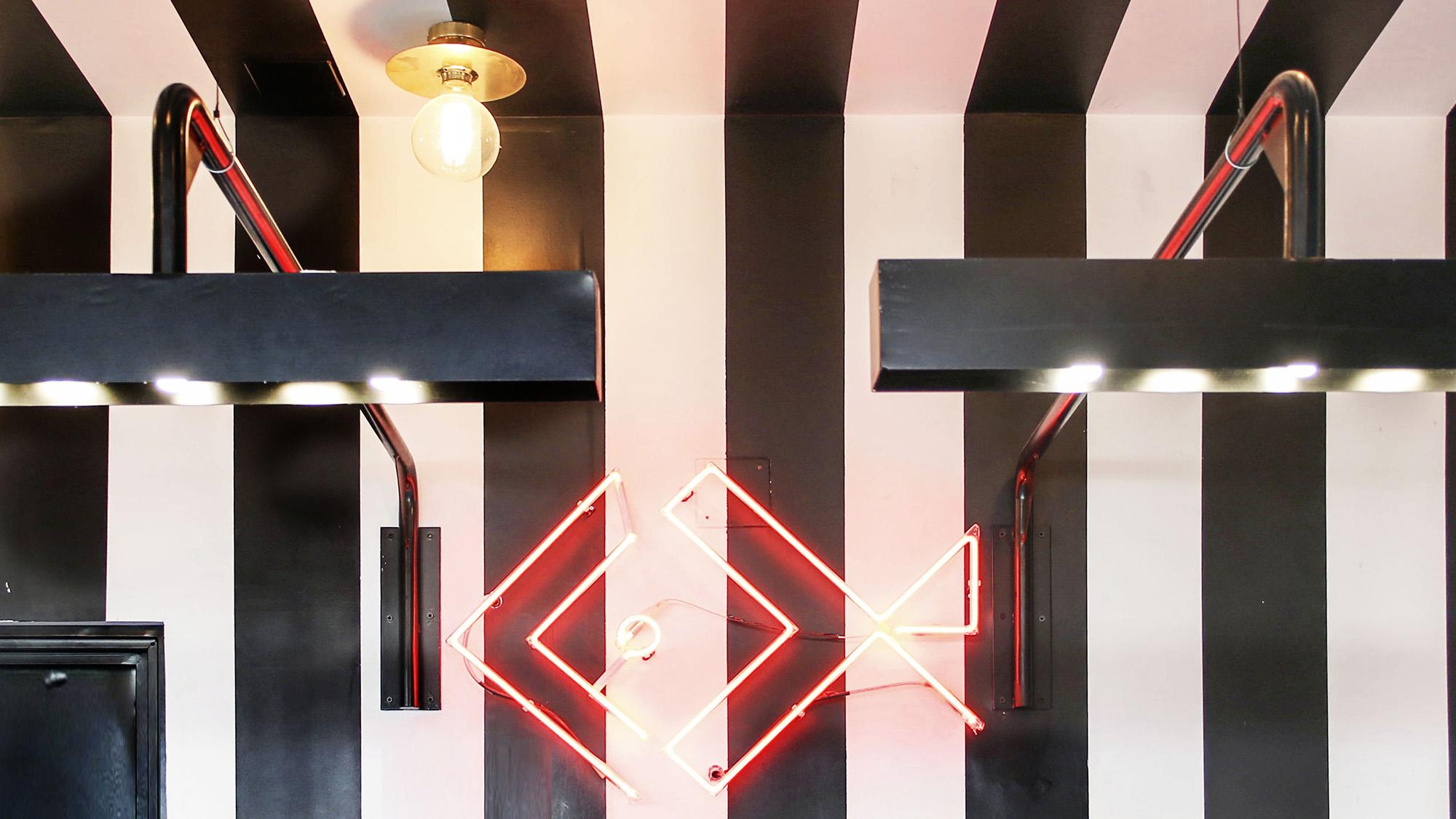 logo de restaurante cevichévere en neón rojo sobre pared de rayas blancas y negras con lámparas modernas y apliques en oro, todo decorado por Belén Ferrándiz