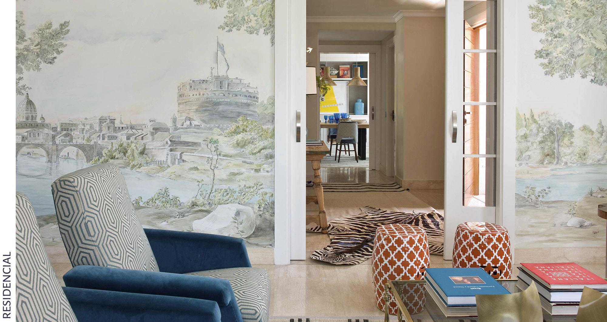 Mural pintado en la pared con dibujo de bosque, decoración moderna combinando elementos clásicos y modernos, taburetes rojos y sillas tapizadas en dos telas, todo obra de Belén Ferrándiz